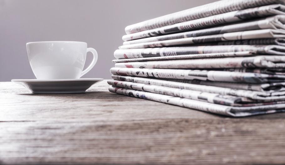 Weigel GmbH - Zeitungen mit Tasse auf einem Holztisch